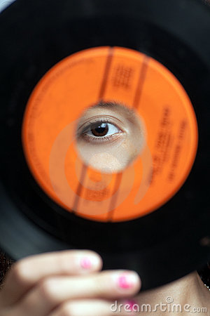 Girl looking through hole in record
