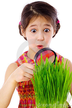 Girl looking through a magnifier at the grass