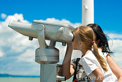 Girl looking through pay-to-use telescope