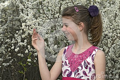 Girl looking and touching white flowers