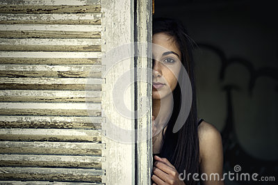 Girl looking through a window shutter