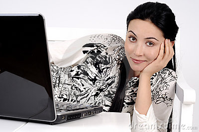 Girl looking at you with a computer laptop on bed