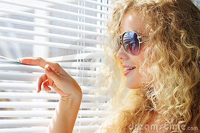 girl looks through the blinds