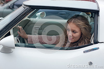 Girl looks in a car mirror