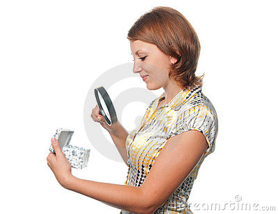 Girl looks at a gift through a magnifier