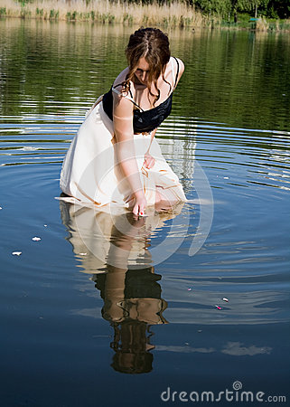 girl looks at his reflection in the water royalty free