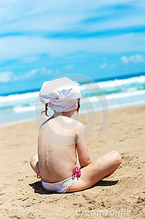 Girl looks at the sea sitting on the sand