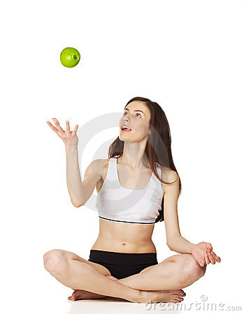 Girl in the lotus position throws apple