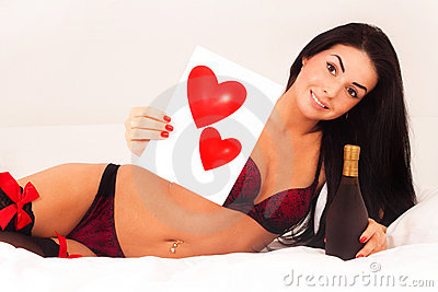 Girl lying in bed with gifts, cards, hearts, wine