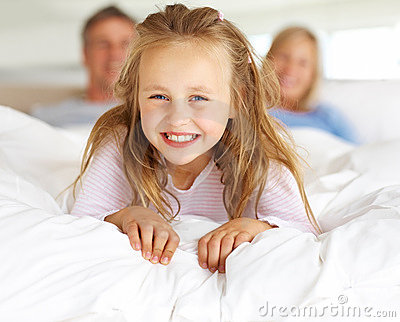 Girl lying on bed with her parents in background