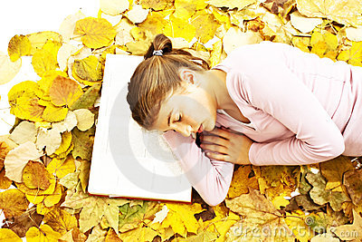 Girl lying down reading book with leaves around