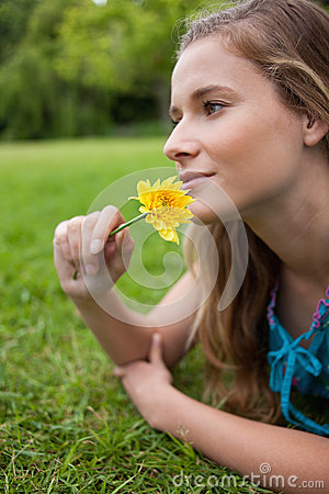 Girl lying on the grass while smelling a flower
