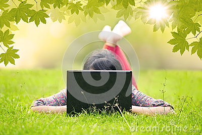 Girl lying on grass using laptop outdoor