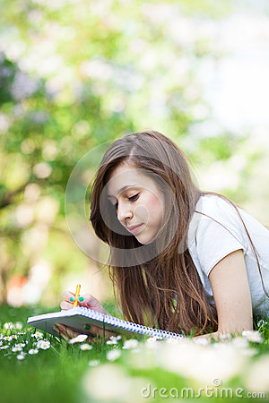 Girl lying on grass with workbook