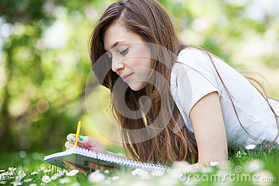 Girl lying on grass with workbook and pencil