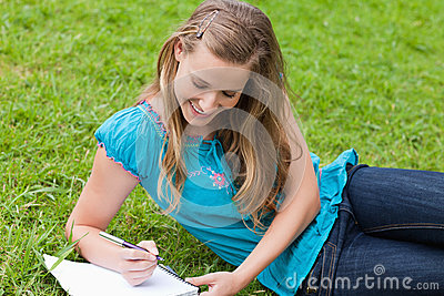 Girl lying on the grass while writing