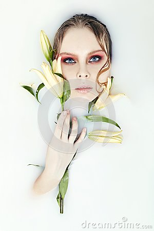 Free Girl Lying In Bath With Milk And Lily In His Hands. Portrait Of Woman In White Water And Flowers In Hand. Skin Rejuvenation, Body Royalty Free Stock Photo - 109197555
