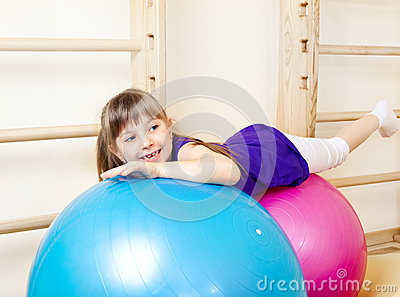 Girl lying on large gymnastic balls