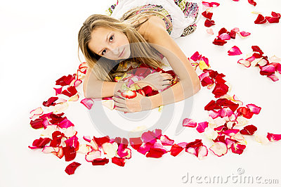 Girl lying with rose petals in view of the heart