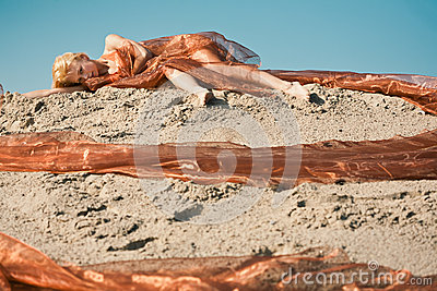Girl lying on sand in orange cloth