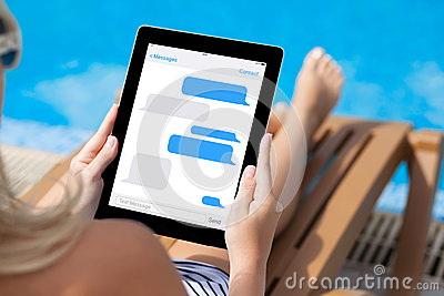 Girl lying on a sun lounger by the pool with a computer tablet w