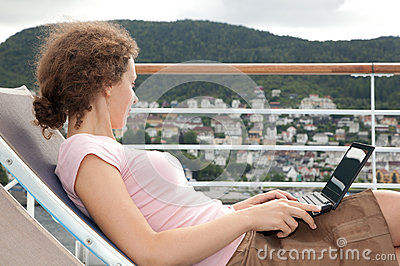girl lying on sunbed with laptop on deck