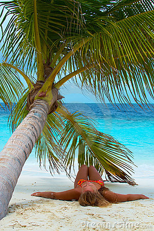 Girl is lying under palm tree. Luxury Holidays.