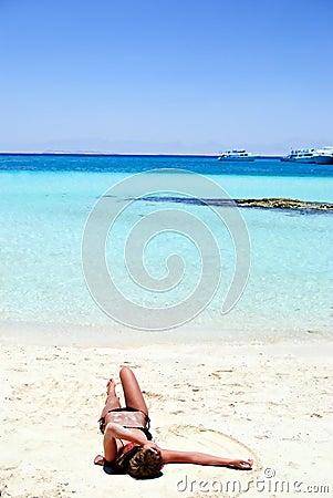 Girl lying on white sand beach