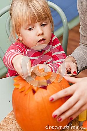 Girl making halloween pumpkin