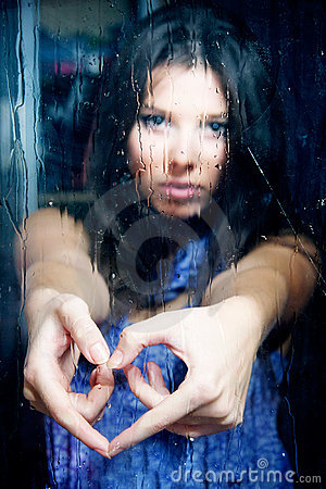 Girl making heart from fingers behind wet window