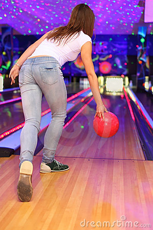 Girl making throw of ball in bowling club