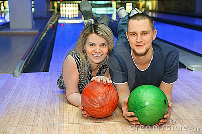 Girl and man lie on parquet in bowling club