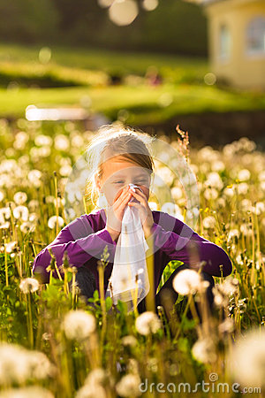 Girl in meadow and has hay fever or allergy