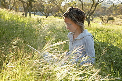 Girl on the meadow relaxing and using a laptop