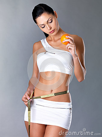 Girl measures figure and holding orange