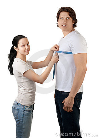 Girl measuring the chest of handsome muscular man