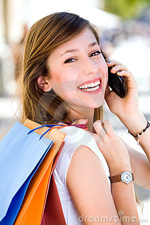 Girl with mobile phone and shopping bags