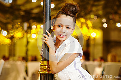Girl-model stands, leaning decorative lamppost