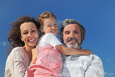 Girl, mother and grandfather smiling and embracing Stock Photo