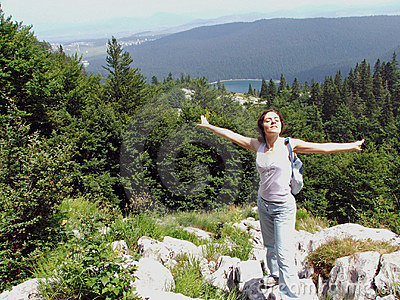 Girl at the mountain top with arms wide spread