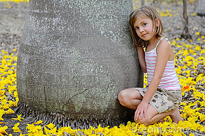 Girl near the big tree surrounded by yellow flower