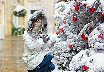 Girl near Christmas tree covered with snow