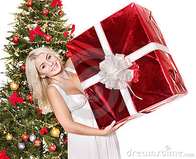 Girl near christmas tree holding red gift box.