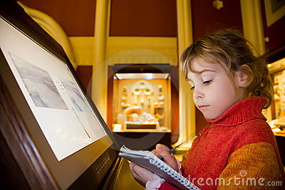 Girl near monitor writes at excursion in museum