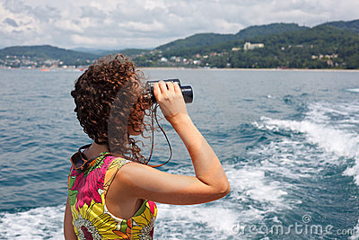 Girl observing in binocular sea coast