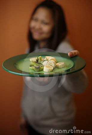 Girl Offering a Plate of Kiwi and Banana
