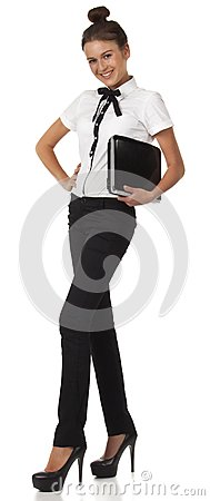 Girl in office attire stands and holds a laptop co
