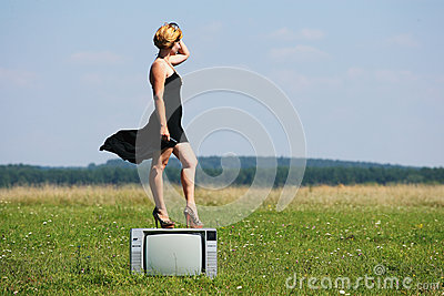 Girl with old tv at the middle of the fields