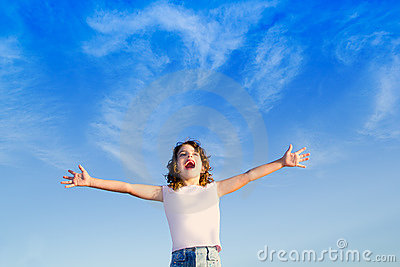 Girl open arms outdoor under blue sky