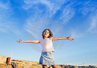 Girl open arms outdoor under blue sky
